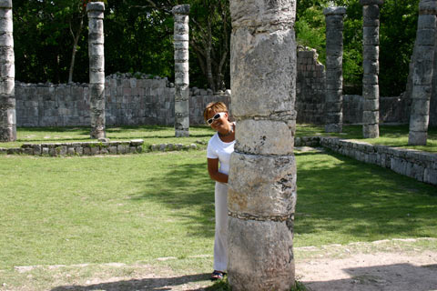 Karina hides behind a column at Chich\'en Itzá