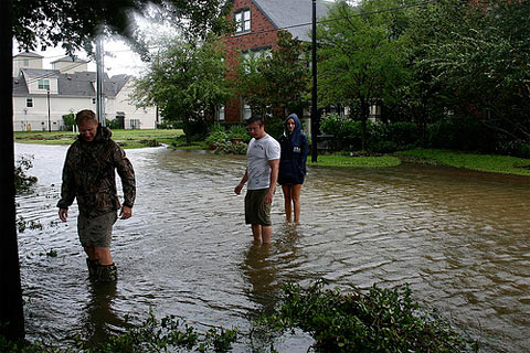 Neighbors work to clear storm drains on the flooded streets of Midtown Houston after Hurricane Ike's passage.