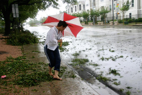A woman fights high winds in Midtown Houston after clearing a blocked storm drain.